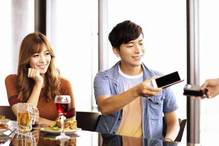 young man paying  by smart phone in restaurant Imagens