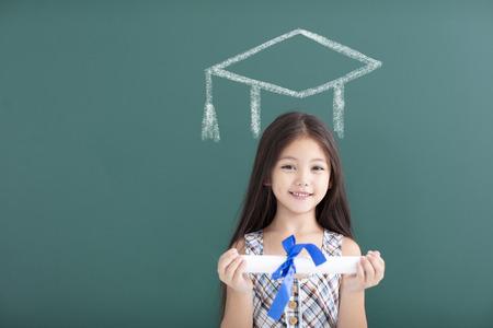 niña feliz en el casquillo de la graduación con el concepto de educación