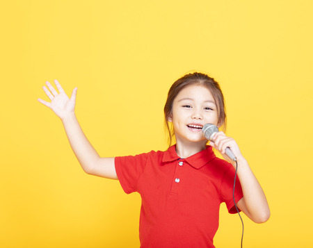 happy little girl singing on yellow background
