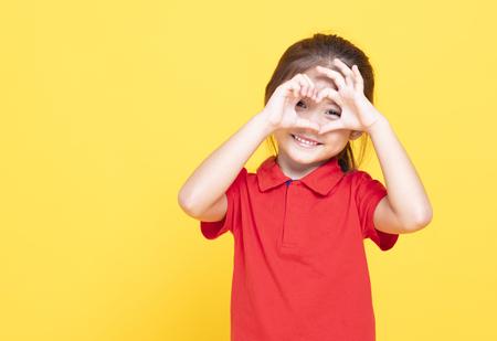 happy little girl making heart shape by hand Stockfoto