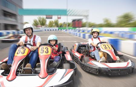 familia feliz conduciendo kart en la pista Foto de archivo