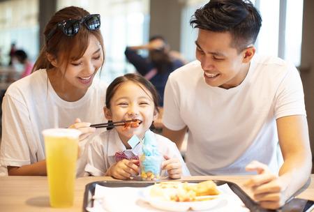 Glückliche Familie, die das Abendessen im Restaurant genießt.