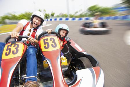 Vater und Tochter fahren Go-Kart auf der Strecke Standard-Bild
