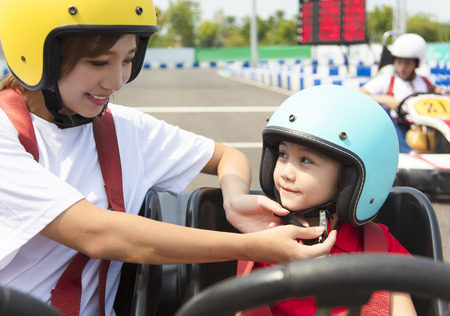 Mother attaching daughters  helmet on go kart race track Standard-Bild
