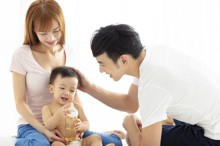happy father and mother talking with baby