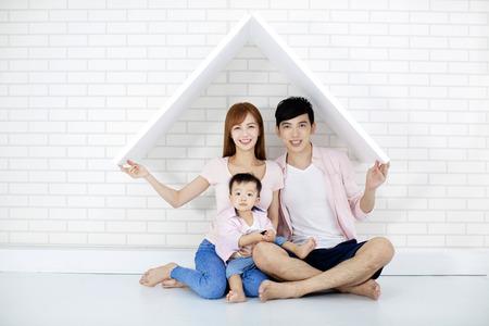 famille heureuse dans une nouvelle maison avec toit
