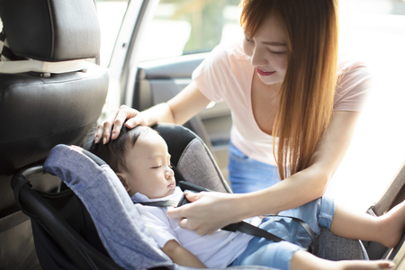 Mother securing baby in the car seat
