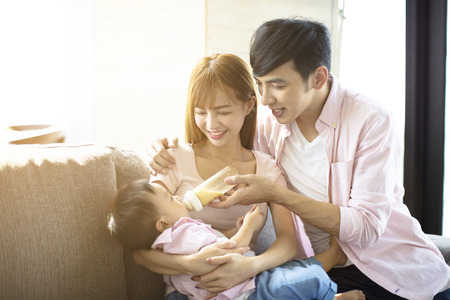 happy father and mother feeding baby from bottle