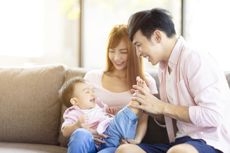 happy family mother and father playing with baby at home 免版税图像