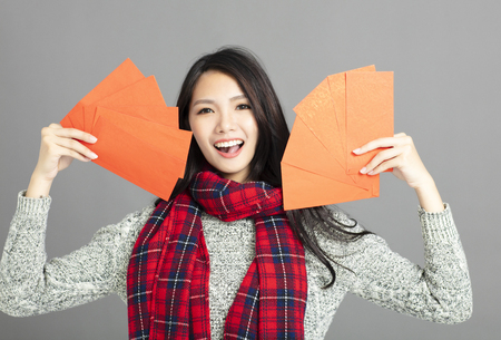 asian woman showing red envelopes for chinese new year
