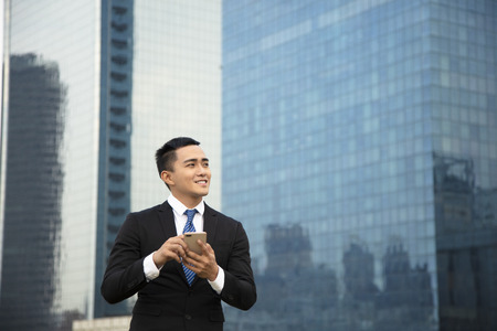 Business man using smart phone owith building background