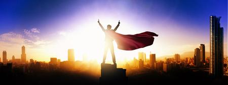 Superheld-Geschäftsmann mit Blick auf die Skyline der Stadt bei Sonnenaufgang Standard-Bild