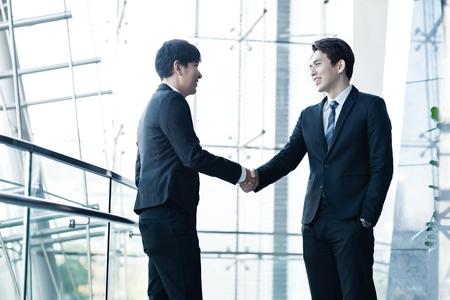 Zwei selbstbewusste Geschäftsleute, die Hände schütteln und lächeln