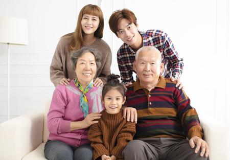 happy three generations asian family on sofa
