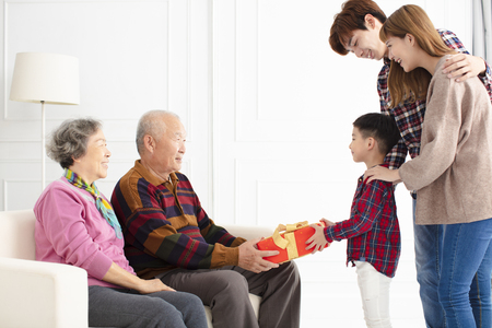 grandchild with parents giving a gift to grandparents 版權商用圖片 - 115369852