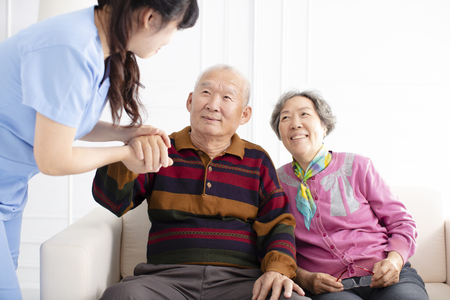 Health visitor and  senior couple during home visit 免版税图像