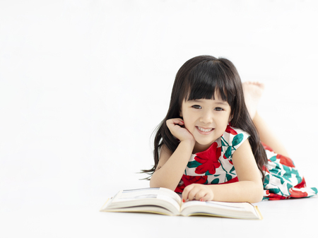 smiling little  girl with book lying on the floor