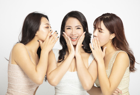 Three women telling whispering and secret gossip