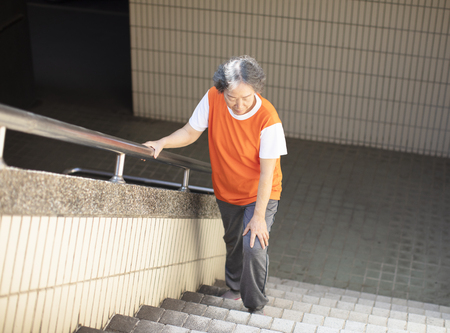 female senior Suffering from knee Pain  on stair