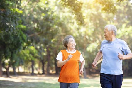 Heureux couple de personnes âgées courant dans le parc Banque d'images