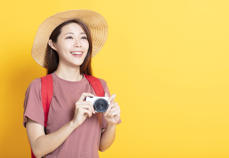 happy young woman in summer hat and holding camera