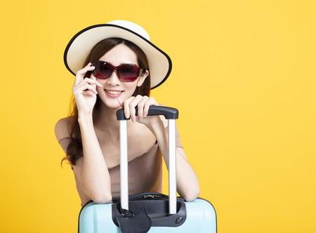 gelukkige toeristenvrouw in de zomerhoed die zonnebril en koffer houdt Stockfoto