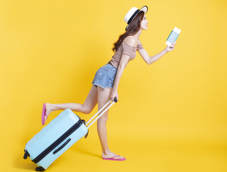 happy tourist woman in summer hat with passport and suitcase