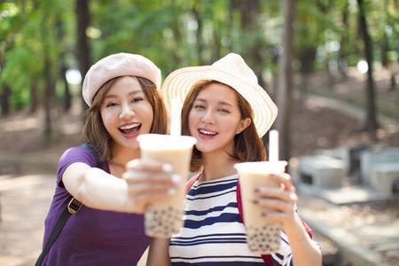 happy girls drinking bubble tea and enjoy summer vacation Stock Photo - 119884416