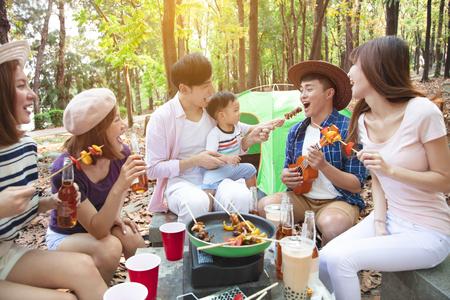 szczęśliwa grupa młodych przyjaciół ciesząca się piknikową imprezą i kempingiem