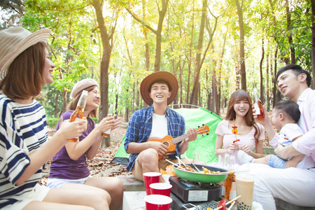 happy asian young group enjoying picnic party and camping