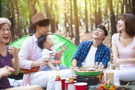 Feliz grupo de jóvenes amigos disfrutando de una fiesta de picnic y acampar Foto de archivo