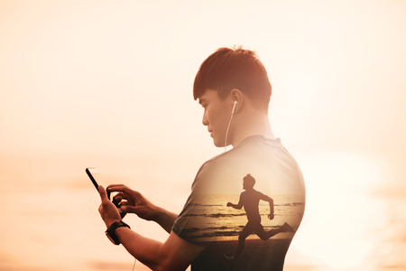young Man running on beach and checking Heart Rate Monitor On smart phone concept