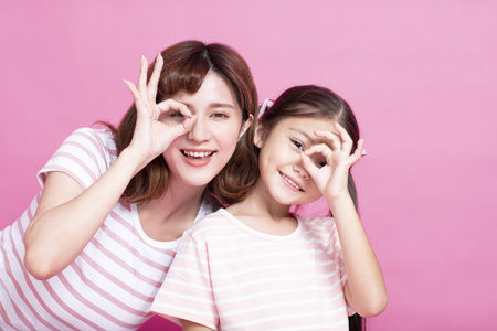 happy mother and daughter holding fingers near eyes