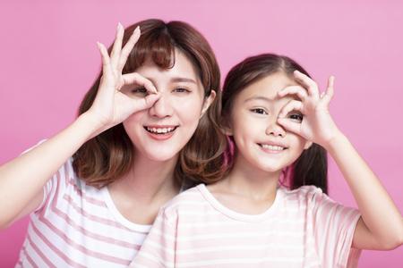 feliz madre e hija sosteniendo los dedos cerca de los ojos