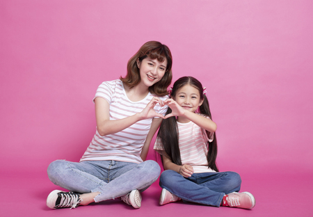 feliz madre e hijo haciendo mano corazón