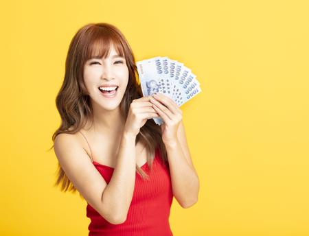 Porträt einer fröhlichen jungen Frau, die das Geld zeigt