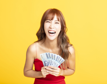 Portrait of  cheerful young woman showing the  money