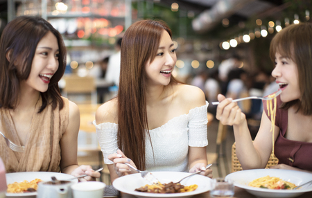 Gelukkige vrienden die dineren in restaurant