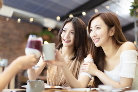 happy Friends Celebrate with  Toast and Clink in Restaurant