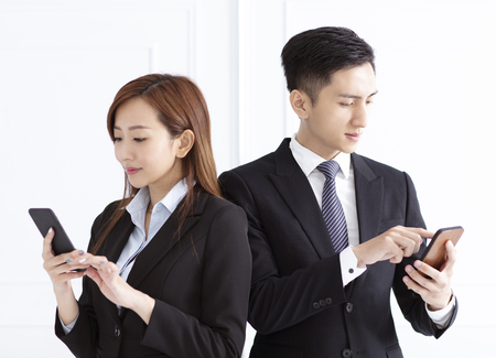Young smiling businesswoman and businessman watching smart phone