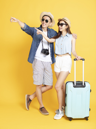 Full length of Asian Couple with travel luggage and camera looking something