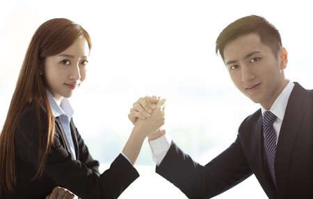 business woman VS business man arm wrestling