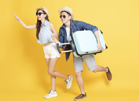 happy young Couple running with travel luggage