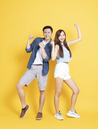 happy young couple in summer casual clothes dancing isolated on yellow