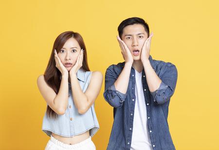 Schockierter Mann und Frau, die schreien und das Gesicht berühren