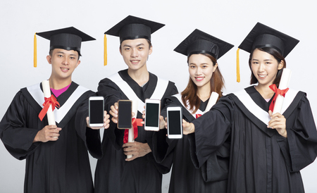 Grupa absolwentów pokazujących inteligentny telefon