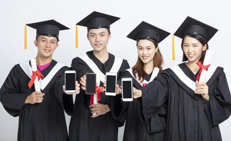 Grupo de estudiantes graduados que muestran teléfonos inteligentes.