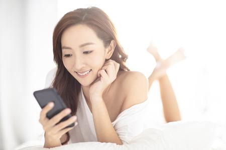 junge lächelnde Frau, die Handy auf dem Bett beobachtet