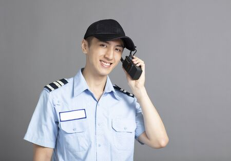 Security guard using portable radio transmitter Stockfoto