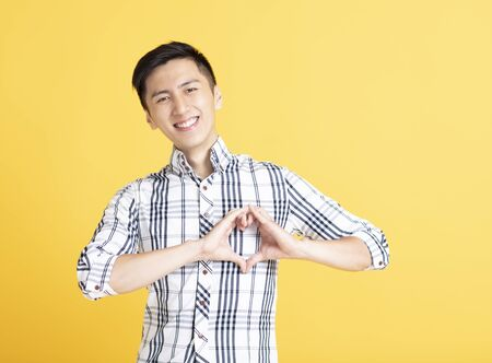 Young man shows heart-shaped gesture on his chest Stock fotó